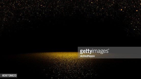 twinkling golden glitter falling on flat surface lit by spotlight : Stock Photo