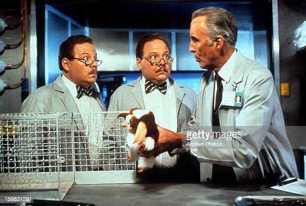 Twins Don Stanton and Dan Stanton watch as Christopher Lee takes Gizmo out of his cage in a scene from the film 'Gremlins 2 The New Batch' 1990