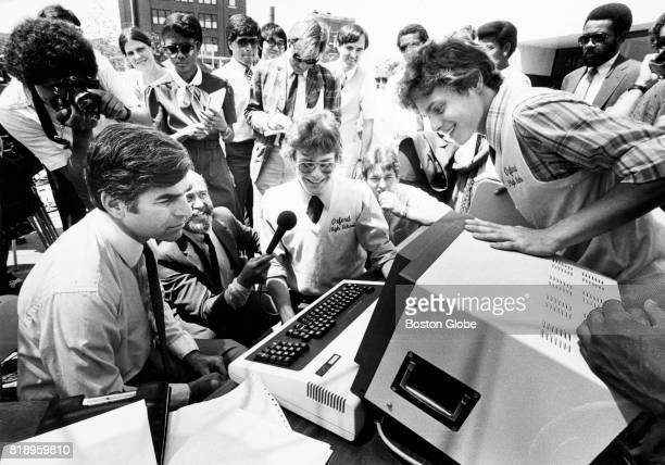 Twins Garry Goodell and Jim Goodwell explain computer program to Governor Michael Dukakis at a press conference at Digital Equipment Corp in the...