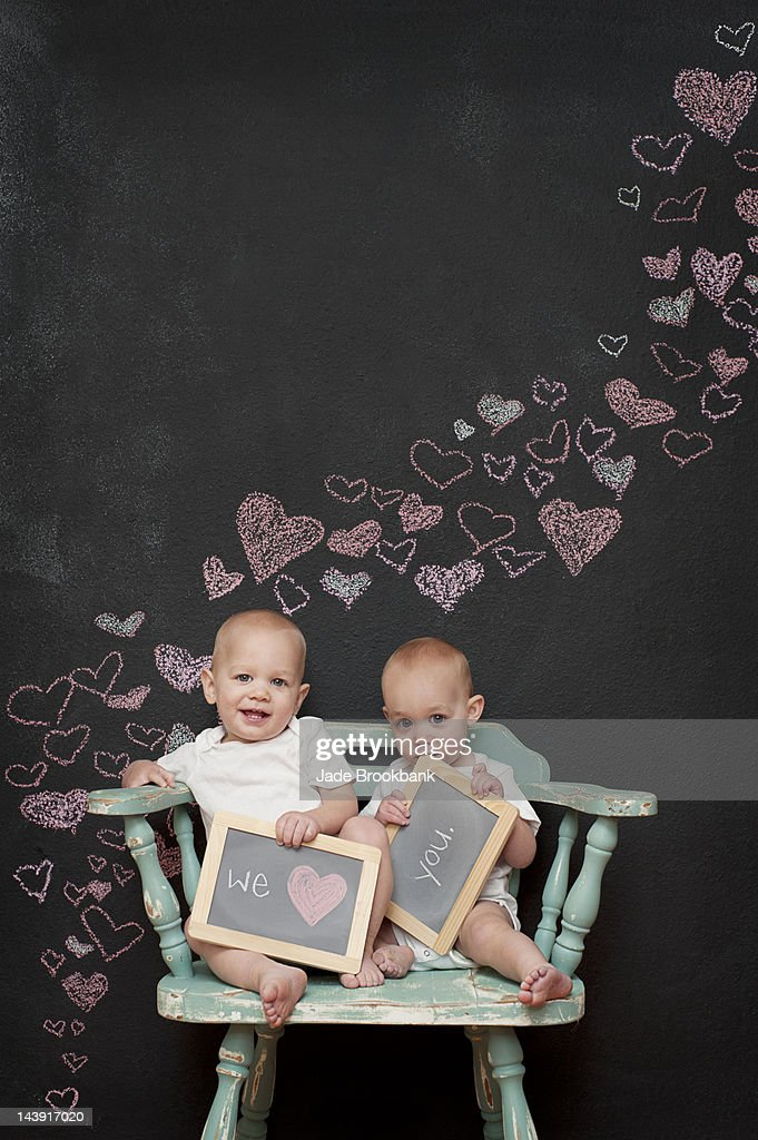 Twins holding love you sign for valentine's day : Stock Photo