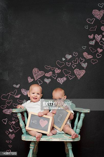 Twins holding love you sign for valentine's day