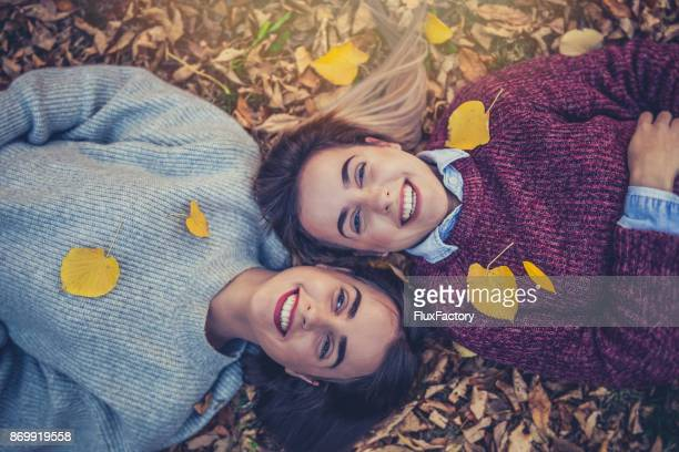 Twins lying in autumn leaves