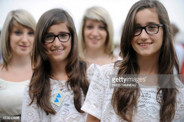 Twins pose in the Fete des Jumeaux a gathering of twins triplets and quadruplets in Pleucadeuc France on August 15 2014 AFP PHOTO/ FRED TANNEAU