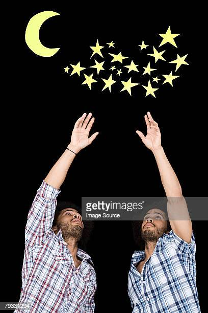 Twins reaching for stars