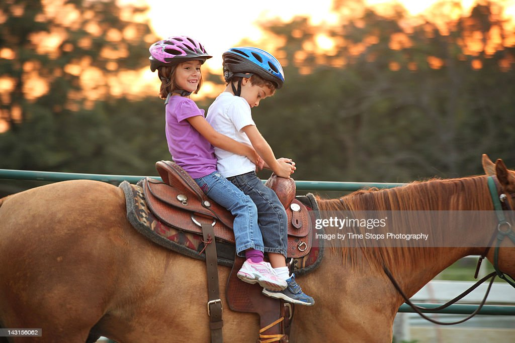 Twins riding horse together