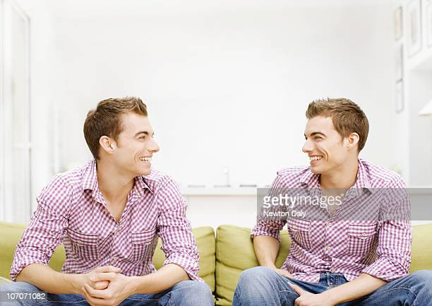 Twins sitting on sofa, smiling