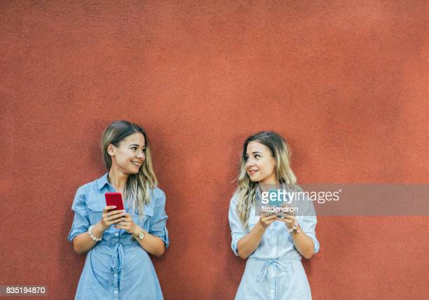 Twins texting in the city