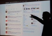 Twitter CEO Evan Williams is seen silhouetted against a screen as he shows off the newly revamped Twitter website on September 14 2010 at Twitter...