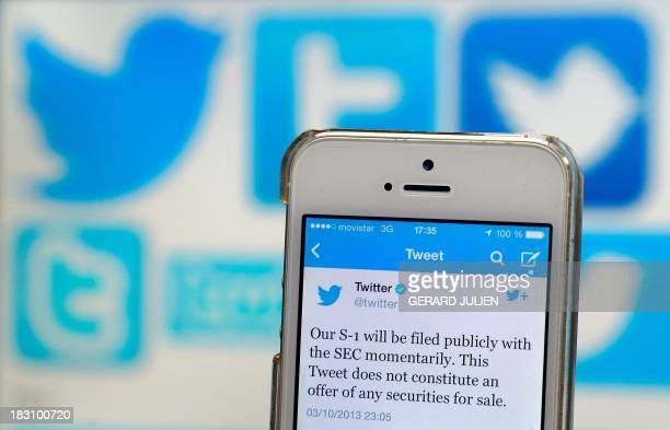 A Twitter tweet announcing the company's planned initial public offering is pictured on a mobile telephone backdropped by various twitter logos in...
