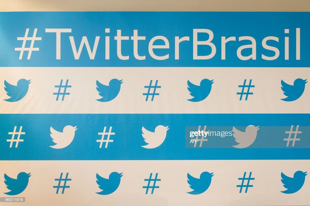 Twitter's brand marks are seen as background of the speakers during their press conference in Sao Paulo, Brazil on Februrary 20, 2013. Twitter began hunting for clients in Brazil with an eye on the upcoming Fifa World Cup Brazil 2014 and the Rio Olympic Games 2016. AFP PHOTO/Yasuyoshi CHIBA