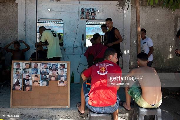 Two 2 young Brazilian men sitting on a bench waiting to have their hair cut Young independent barber shop hair stylist in the street for the young...