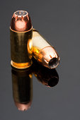 Two .45 Caliber Hollowpoint Bullet on a Reflective Grey Backgrou