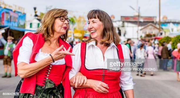 Two active senior women in traditional Bavarian dirndl dresses having great fun visiting the Oktoberfest 2017 in Munich.