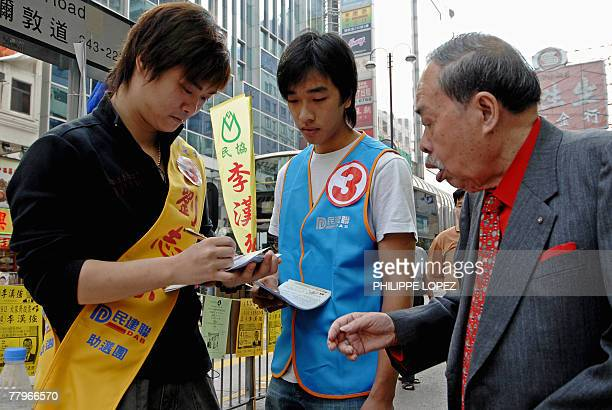 Two activists of the Democratic Alliance for the Betterment and Progress of Hong Kong distribute leaflets to pedestrians during the fouryearly...