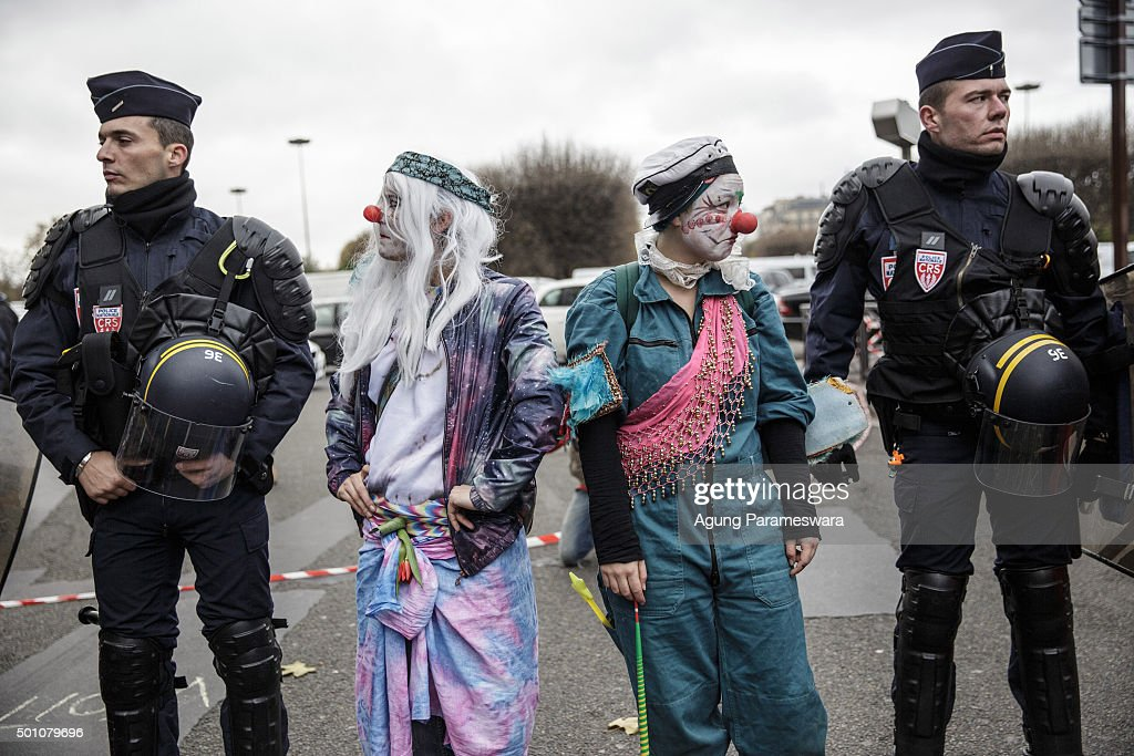 Two activists perform beside the police as they attend a demonstration near the Arc de Triomphe at the Avenue de la Grande Armee boulevard on December 12, 2015 in Paris, France. The final draft of a 195-nation landmark agreement on climate has been submitted at the United Nations conference on climate change COP21, aimed at limiting greenhouse gas emissions and keeping planetary warming below 2.0 degrees Celsius.