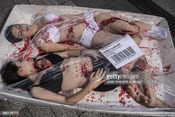Two activists splattered with red paint to represent blood lie in a container reading 'human meat' during a demonstration by the animal liberation...
