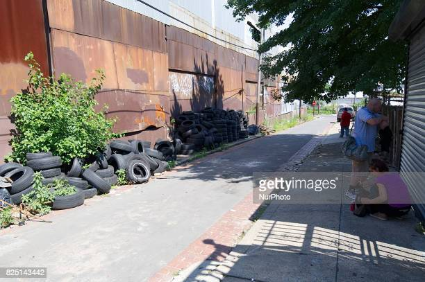 Two addicts find shade as they attend to themselves in an alley near the large heroin camp alongside the active Conrail train track in the Kensington...