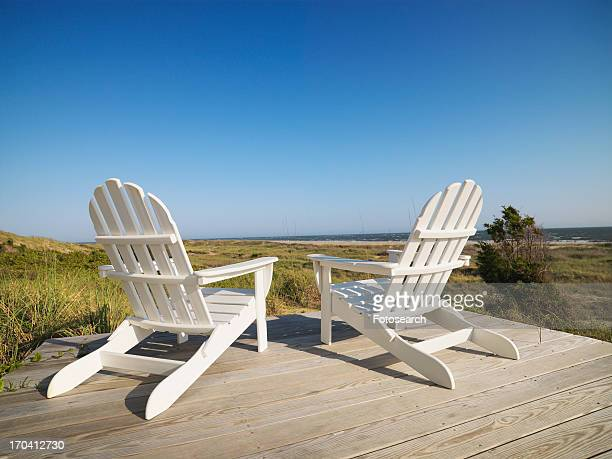 Two adirondack chairs on wooden deck overlooking beach at Bald Head Island, North Carolina