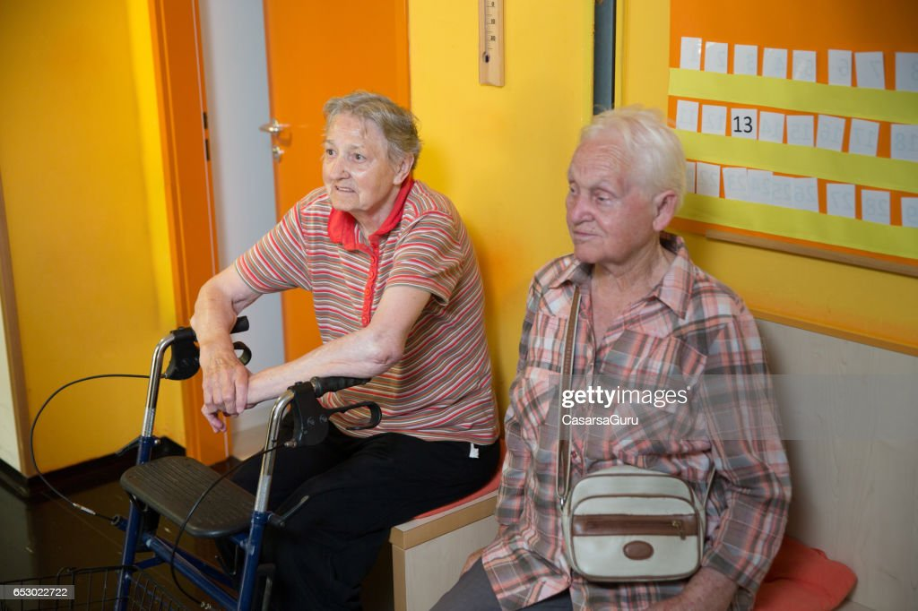 Two Adult Senior Waiting In The Hall Of Care Center : Stock Photo