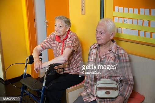 Two Adult Senior Waiting In The Hall Of Care Center : Stock-Foto