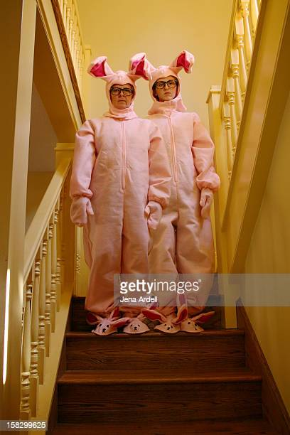 Two Adults Wearing Pink Bunny Suits on Staircase