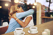 Two multi ethnic affectionate girl friends embracing as they sit in a coffee shop enjoying a cup of coffee together