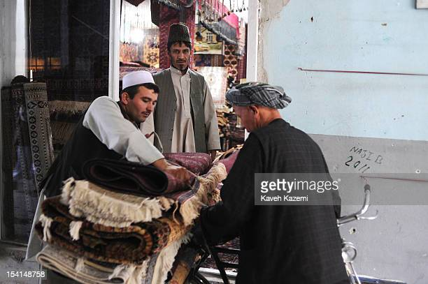 Two Afghan men deliver rugs carried on a bicycle to a shopkeeper in Chicken Street on October 17 2011 in Kabul Afghanistan Chicken Street has been a...