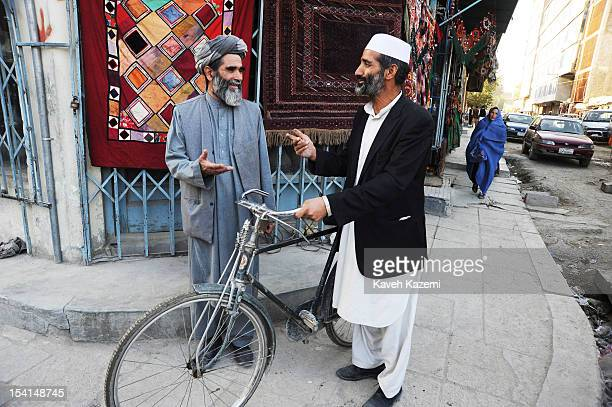 Two Afghan men talk at a corner where rugs are displayed on a wall in Chicken Street on October 17 2011 in Kabul Afghanistan Chicken Street has been...