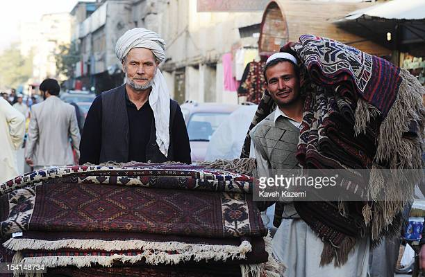 Two Afghan porters carry rugs in Chicken Street on October 17 2011 in Kabul Afghanistan Chicken Street has been a focus for Afghanistan's tourists...