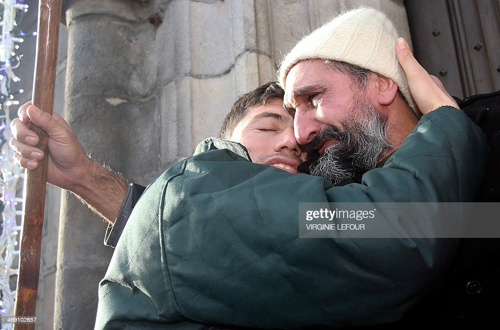 Two Afghan refugees embrace as Afghan refugees and Belgian activists take part in a protest march organized by the 'Afghan Collective', on December 23, 2013, in Mons. Some 200 Afghan asylum-seekers and their supporters set up camp late December 22 in Belgium's western town of Mons, demanding to see Belgian Prime Minister Elio Di Rupo to press for residency papers.