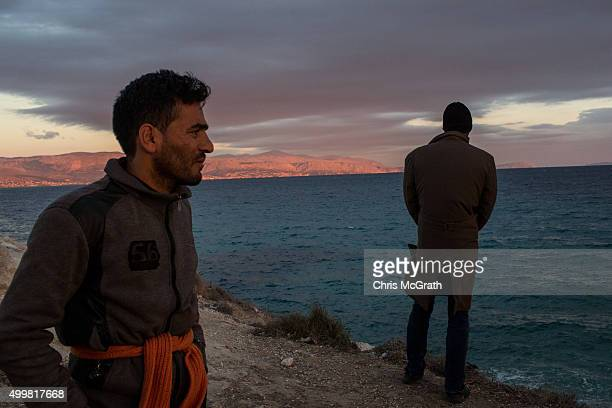Two Afghan refugees look out at Chios Island as they wait for a boat at a launching point in the coastal town of Cesme on December 3 2015 in Cesme...