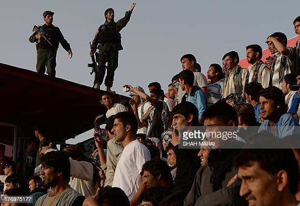 Two Afghan security force personnel stand guard as football fans watch their team play against Pakistan at the Afghanistan Football Federation...