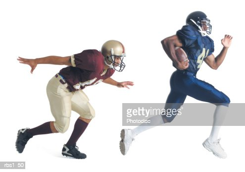 two african american american football players from opposing teams are running as the one in front holds the football and the other tries to catch him