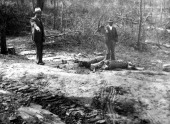 Two African American men point to tire tracks at the scene of a lynching Georgia 1930