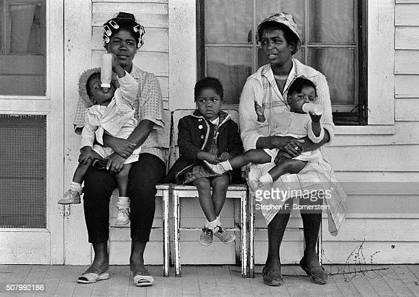 Two AfricanAmerican mothers with babies drinking from milk bottles and a wellbehaved child seated on the porch watching the Selma to Montgomery...
