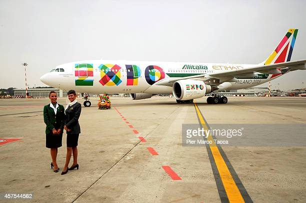 Two air hostesses pose for a photo in front of the Airbus 330 Alitalia during the press conference at Malpensa Airport on October 20 2014 in Milan...