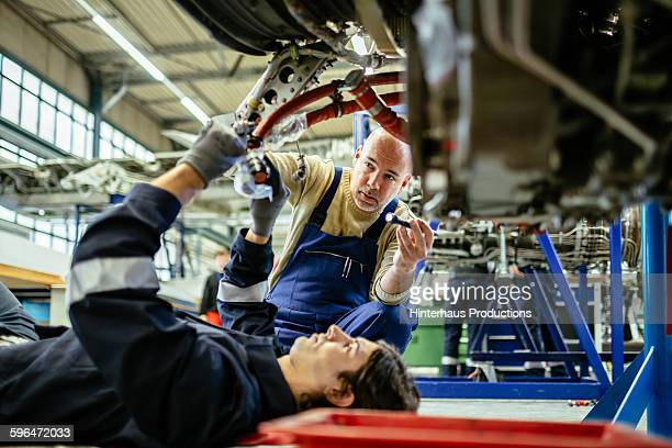 Two Aircraft mechanics working on a jet engine.