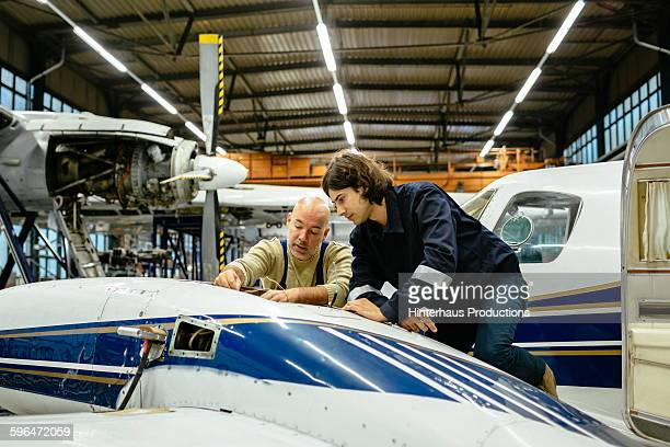 Two aircraft mechanics working on small airplane