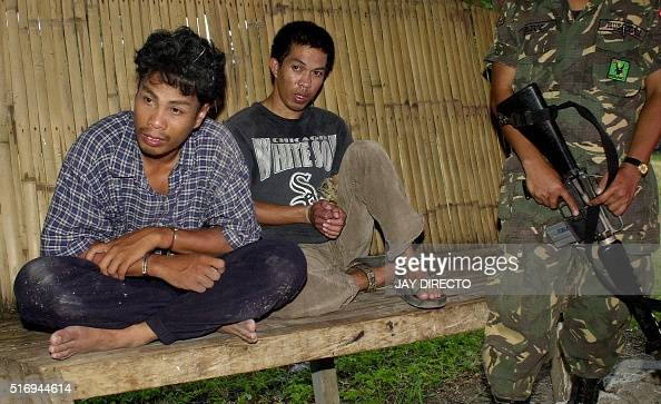 Two alleged members of the Muslim extremist group Abu Sayyaf are detained 19 September 2000 after government agents nabbed them in Taluksangay...