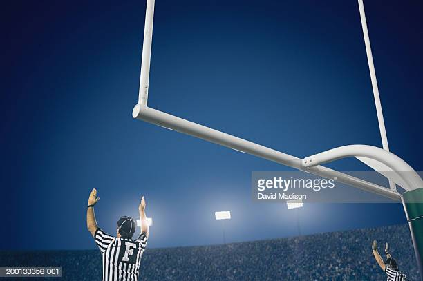 Two American football referees giving touchdown signal, rear view
