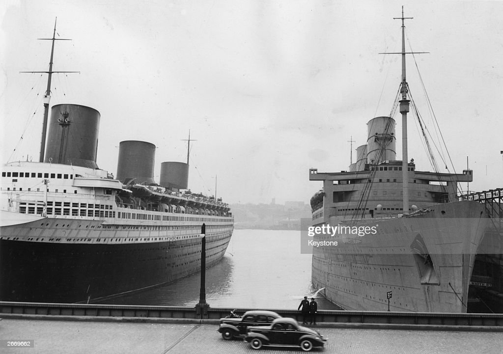 Two American policemen keep an eye on the two great liners Normandie of the French CGT and Queen Mary of Cunard White Star currently moored at the...