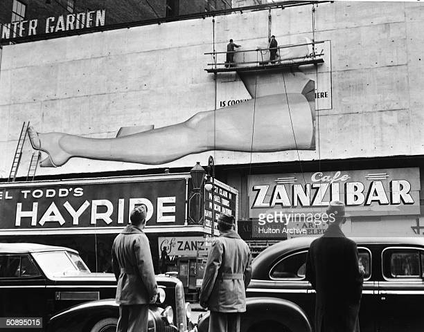 Two American soldiers and a civilian in a fedora watch workers on a scaffold hang a billboard advertisement featuring a woman's bare legs above the...