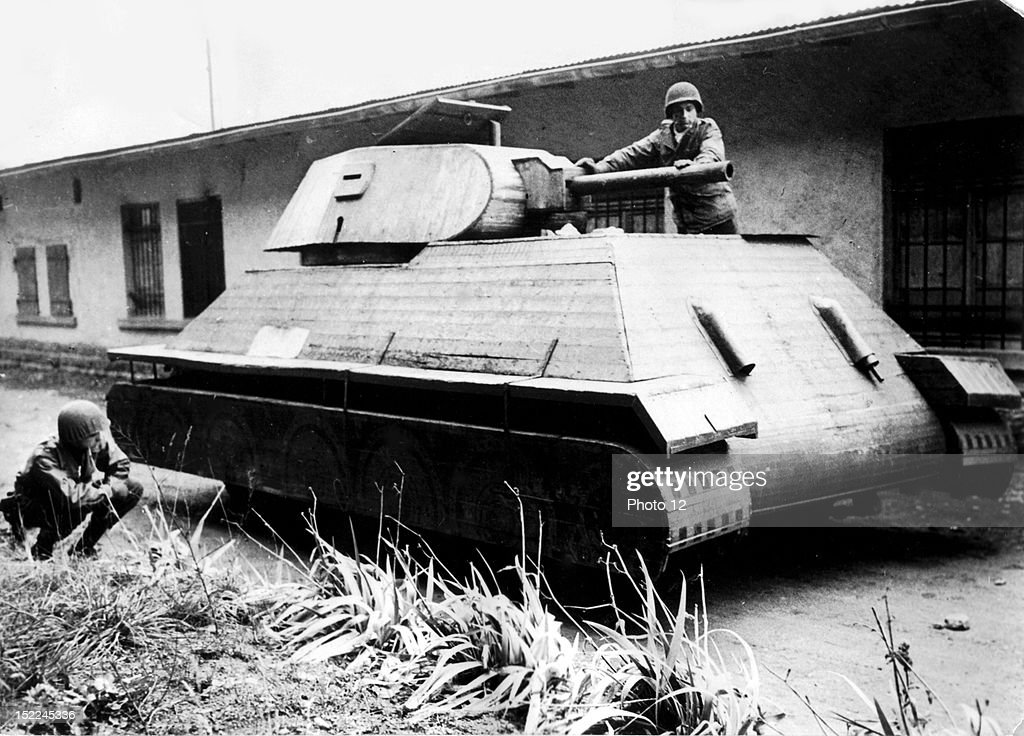 Two American soldiers inspect a dummy German tank fashioned of wood and built on the top of a fourton truck in Molsheim area in France