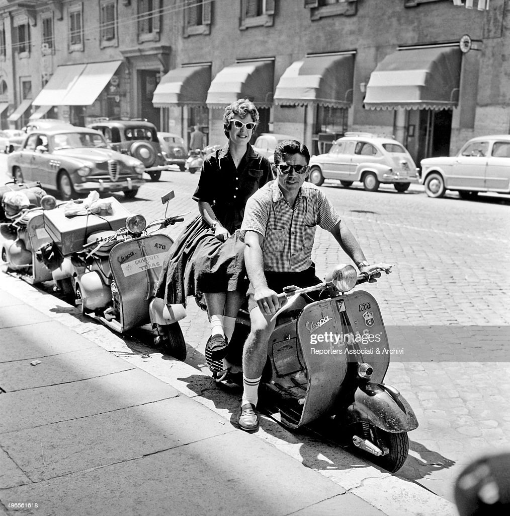 Two American tourists in Rome posing proud of their Vespa saying 'Texas' Rome