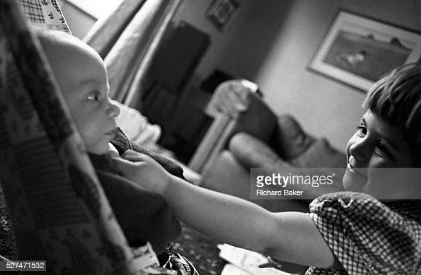 A two and half yearold girl shows affection to her baby brother in the living room of her South London home Reaching out to show her love the big...