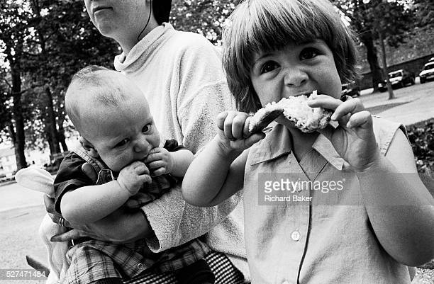 A two and half yearold girl sits next to her threemonth old baby brother eating lunch during a day out with their mother who is seen holding on tight...