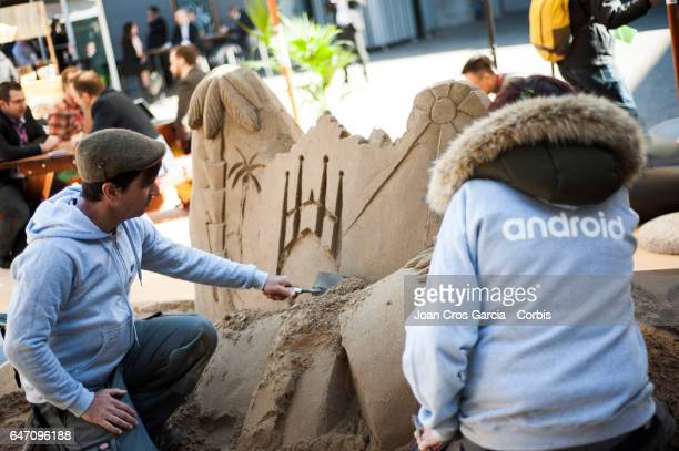 Two Android workers building a Barcelona sand castle during the Mobile World Congress on March 1 2017 in Barcelona Spain