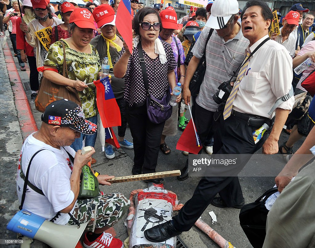Two angry Taiwanese demonstrator trample on a paper-made doll of Lee Teng-hui, former Taiwan president known for his pro-Japanese political stance, during a demonstration in Taipei on September 23, 2012, over a territorial dispute on the island group in the East China Sea. Lee drew fire after telling a Japanese magazine in September that the disputed archipelago belongs to Japan. Hundreds of slogan-chanting Taiwanese activists and their supporters rallied against Japan amid the territorial dispute over the Senkaku island group controlled by Japan, which is also claimed by China and Taiwan under the name Diaoyu. AFP PHOTO / Mandy CHENG