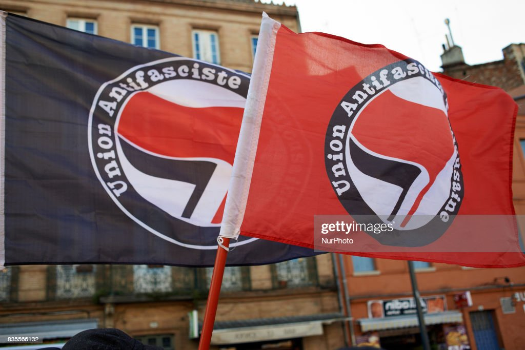 Two antifascism flags during a gathering in Toulouse in solidarity with anti-fascists in Charlottesville after the killing of Heather Heyer by a white supremacist. On August 19th 2017 in Toulouse, France.