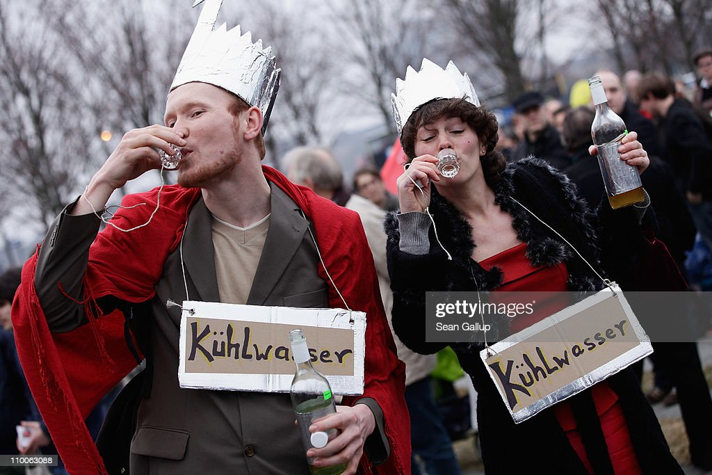Two anti-nuclear activists, sip 'cooling water' they jokingly claimed comes from German nuclear plants during a demonstration in front of the Chancellery on March 14, 2011 in Berlin, Germany. Thousands of anti-nuclear demonstrators, in reaction to the dramatic situation at the Fukushima nuclear facility in Japan, gathered in a coordinated effort in cities across Germany to protest against the government-granted extension of the operational lives of Germany's older nuclear power plants. The debate over the safety of nuclear energy has been reignited worldwide following the earthquake and tsunami in Japan that severely damaged the Fukushima plant and where workers are desperately seeking to prevent a nuclear meltdown.